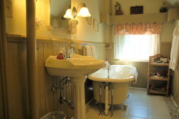 The Clem Studebaker - partial view of the bathroom; clawfoot tub, 3-tiered storage shelf, sink and mirror