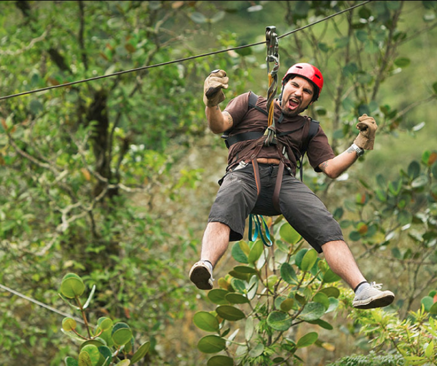 excited guy ziplining through woods