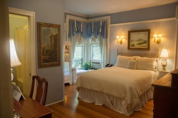 A wide view of the Schuyler-Colfax Room - Bed, bay window, dresser, desk and view into the bathroom with bath/shower combo