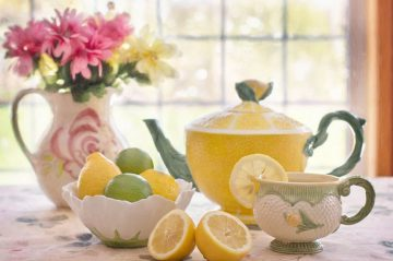 teapot with teacup and bowl of lemons and limes