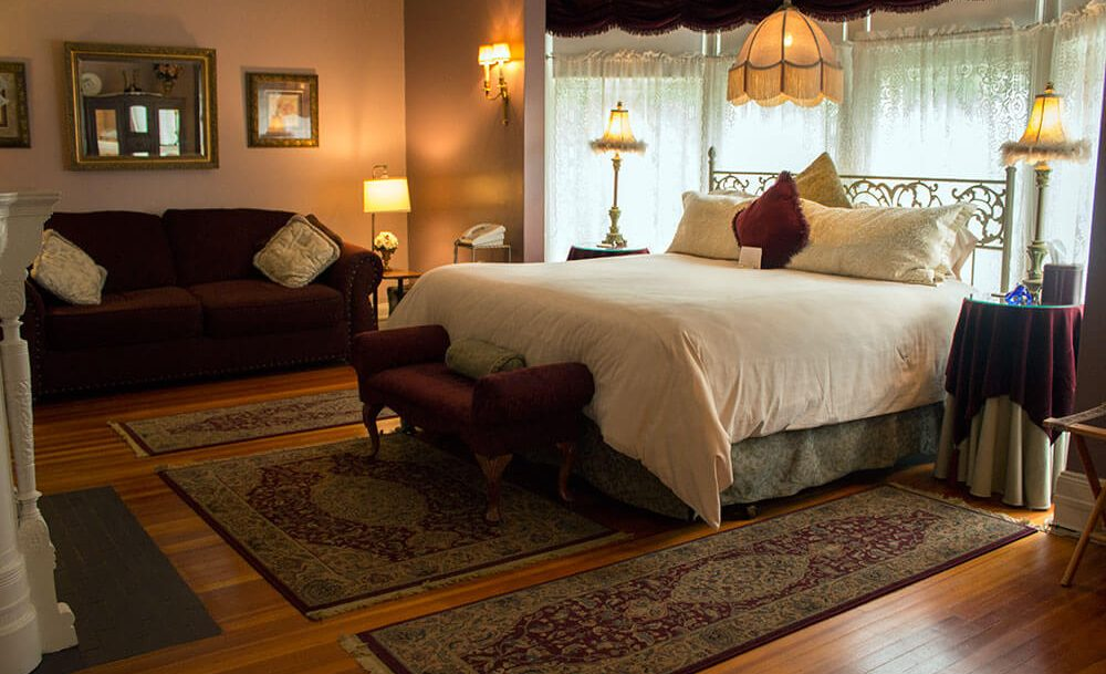 The James Oliver room - bed, footbench, endtables, sofa and fireplace