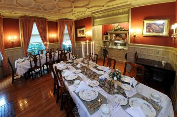Tall shot of the Oliver Inn's dining room set with china, centerpieces and white tablecloths