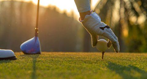 a man picking up a golf tee