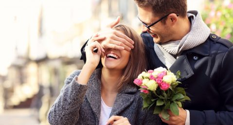 man surprising woman with flowers