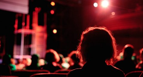 People sitting in a dark theatre watching a live performance.