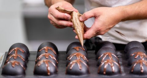 Chocolate maker decorating truffles.